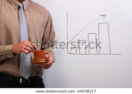 Man in a shirt and a tie holding a plate and a cup while standing next to a drawing of a bar graph.