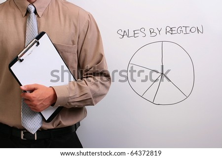 Man in a shirt and a tie standing next to a drawing of a pie chart.