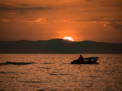 Man in a small boat  in the adriatic sea during sunset