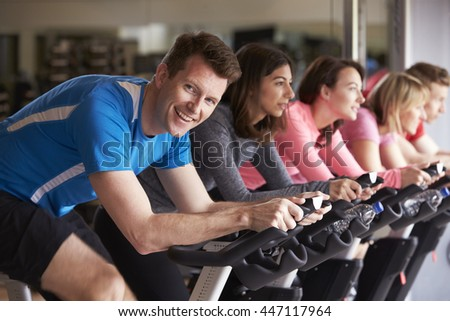 Man in a spinning class at a gym turning to smile at camera