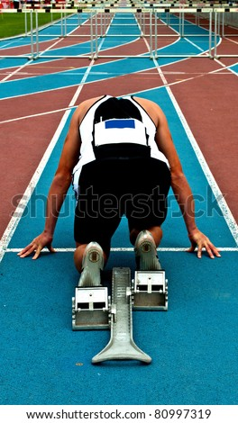 Man in a start block on an athletic track