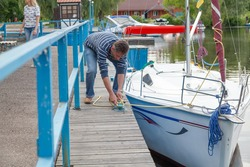 man in a striped shirt secures the mooring rope of a white yacht on a wooden jetty bollard