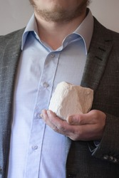 Man in a suit and shirt holding a white stone in front of him.