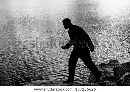man in a suit crossing over rocks at the waterfront