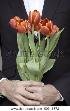 man in a suit holding bunch of red tulips