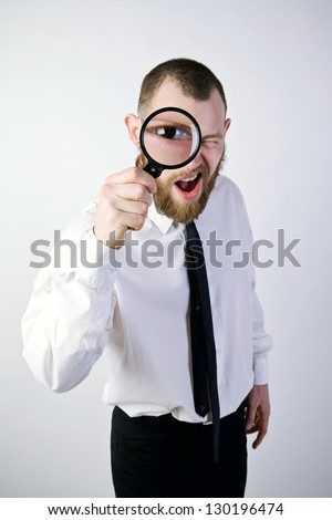man in a suit looking through a magnifying glass