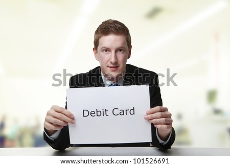 man in a suit sat at a desk look at a  piece of paper with the words debit card printed on it