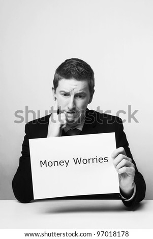 man in a suit sat at a desk look at a  piece of paper with the words money worries printed on it