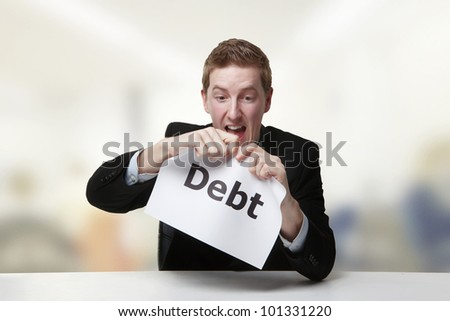 man in a suit sat at a desk ripping a  piece of paper up with the word debt printed on it and looking happy doing so.