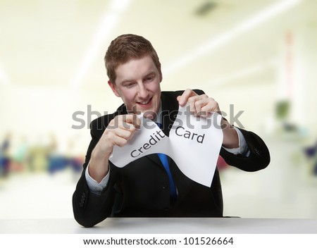 man in a suit sat at a desk ripping a  piece of paper up with the words debit card printed on it and looking happy doing so.