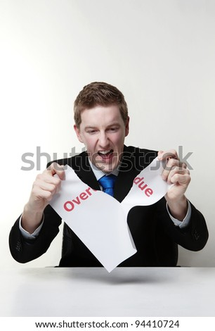 man in a suit sat at a desk ripping a  piece of paper up with the words overdue printed on it and looking happy doing so.