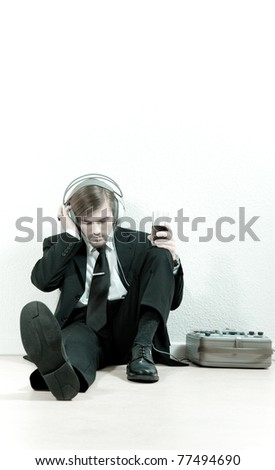 Man in a suit sit on the floor and listen to the music from a old magnetic tape