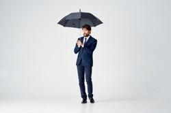 man in a suit standing under an open umbrella