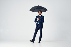 man in a suit standing under an umbrella