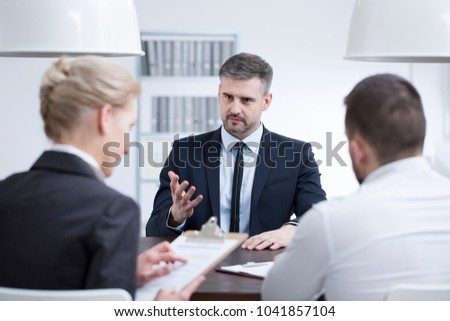 Man in a suit talking about his experience during a job interview in corporation