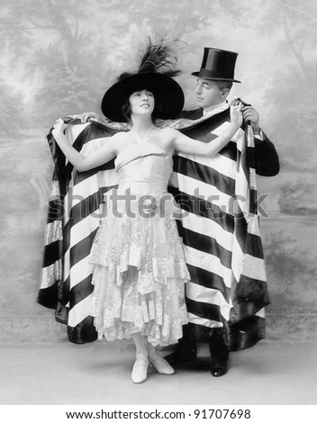 Man in a top hat helping a woman into a cape