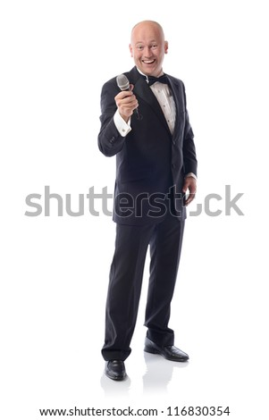 Man in a tuxedo offering microphone isolated on white