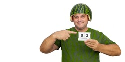 man in a watermelon helmet on his head. funny guy is holding a calendar with the date August 03. National Watermelon Day.