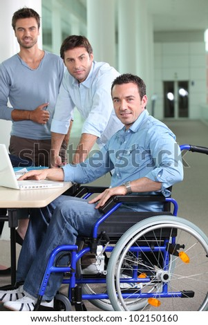 Man in a wheelchair pictured with colleagues