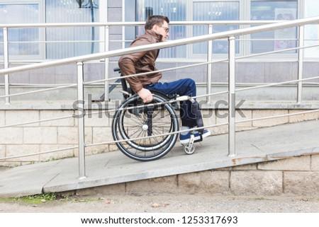 Man in a wheelchair use a wheelchair ramp. Stockfoto ©