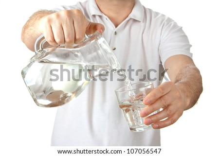 Man in a white shirt pouring water from jug to glass over white background