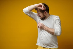 Man in a white t-shirt sniffs his armpits, annoyed by the problem of foul perspiration and body stench. Copy space.