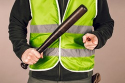 man in a yellow vest, a Builder or a protester with a baseball bat in his hands on a gray background.
