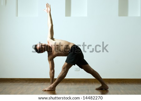 Man in a yoga pose with one arm extended up and the other down and his legs apart. Horizontally framed photograph