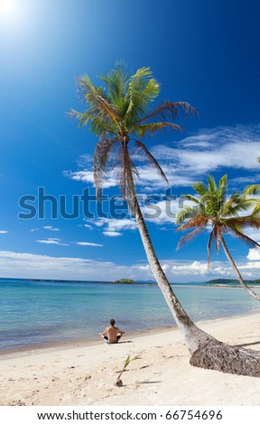 Man in a yoga posture relaxes under palm trees on a lonely beach. Thailand. Island Koh Kood