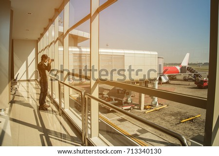 Man in airport. Airplane, view from airport terminal.selective focus,travel concept.