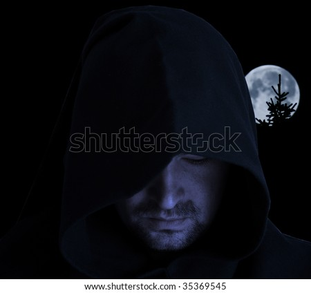 Man in an ancient hood on a full moon background