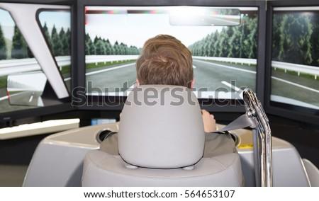 Man in an automotive simulator electric car  #564653107
