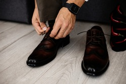 man in an elegant suit tying shoelaces