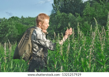 man in an old military uniform standing in the field considering the tall herbaceous plants  #1321257929