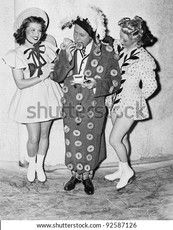 Man in an outfit made of donuts standing between two teenage girls