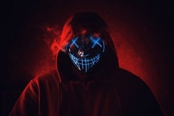Man in angry and scary lighting neon glow mask in hood on dark red background. Halloween and horror concept.