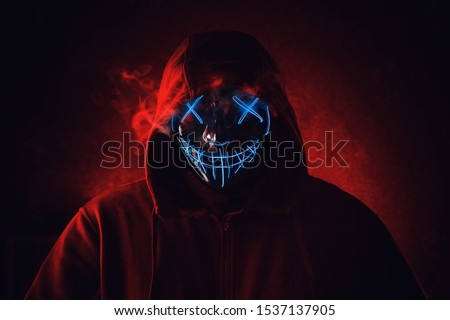 Photo of  Man in angry and scary lighting neon glow mask in hood on dark red background. Halloween and horror concept.