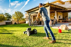 Man in baseball cap mowing green lawn on bright summer day in backyard. Red gasoline can sits nearby on grass ready to refuel mower.