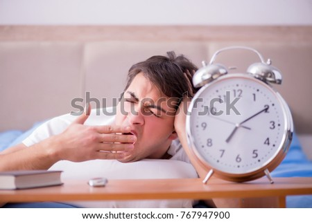 Man in bed frustrated suffering from insomnia with an alarm cloc