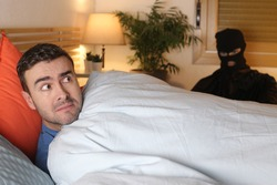 Man in bed surprised by an intruder