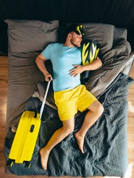 man in bed with yellow suitcase holding flippers and scuba mask overhead top view