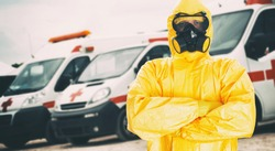 Man in biohazard suit. Ambulance cars on background. Covid-19 quarantine concept.