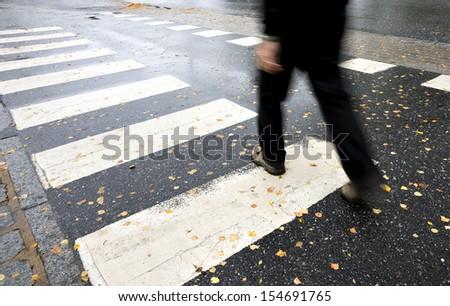Man in black crossing street on wet autumn day