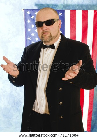 Man in black glasses against the background of american flag gestures