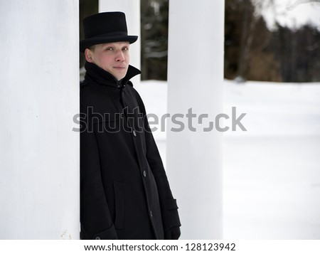 Man in black hat relies on white column - stock photo