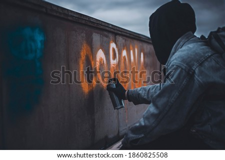 Man in black hood paint corona lettering with orange spray paint . Depressive photo of protest stock photo