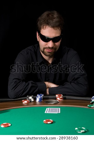 Man in black shirt playing poker in the casino - stock photo