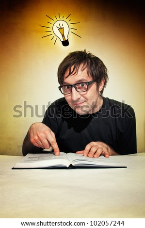 Man in black shirt reading a book with idea bulb above his head