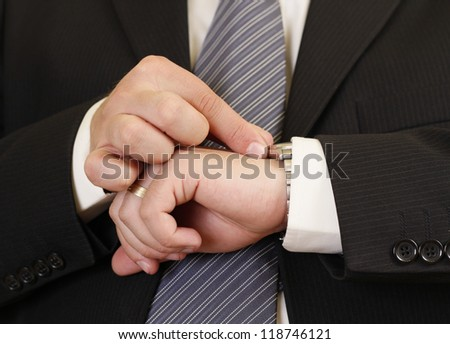 Man in black suit adjusting his watch for being in time to an important event
