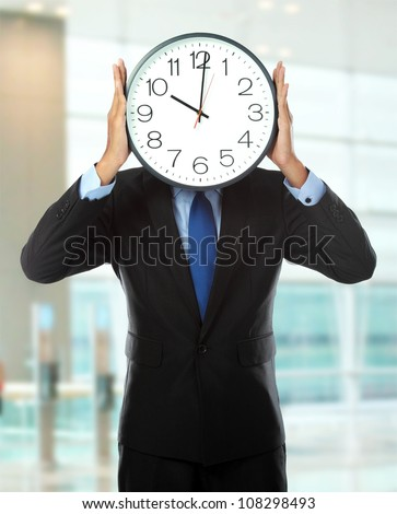 man in black suit holding big clock covering his face in the office